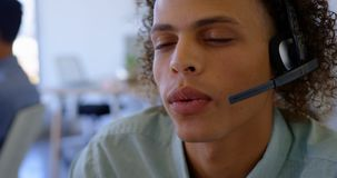 Executivo masculino da misturado-ra?a nova que fala em auriculares na mesa 4k vídeos de arquivo