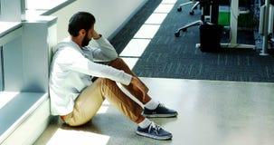 Executivo masculino deprimido que senta-se no assoalho filme