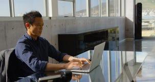 Executivo masculino do negócio asiático novo que trabalha no portátil no escritório 4k vídeos de arquivo