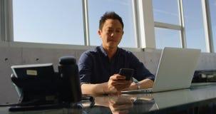 Executivo masculino do negócio asiático que usa o telefone celular na mesa no escritório 4k video estoque