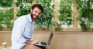 Executivo masculino do retrato que senta-se na mesa e que usa o portátil vídeos de arquivo