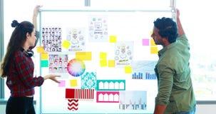 Executivo masculino e fêmea que discute sobre o whiteboard video estoque