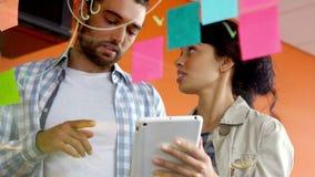 Executivo masculino e fêmea que discute sobre a tabuleta digital video estoque