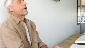 Executivo masculino enrijecido que senta-se na tabela vídeos de arquivo
