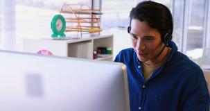 Executivo masculino nos auriculares que trabalham sobre o computador em sua mesa 4k video estoque