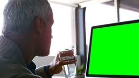 Executivo masculino que bebe ao trabalhar na mesa filme