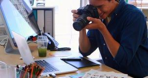 Executivo masculino que clica uma imagem na câmara digital 4k filme