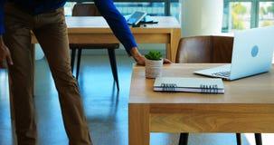 Executivo masculino que faz esticando o exercício ao trabalhar em sua mesa video estoque