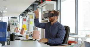 Executivo masculino que usa auriculares da realidade virtual na mesa 4k vídeos de arquivo
