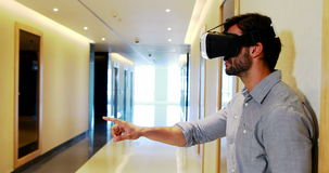 Executivo masculino que usa auriculares da realidade virtual no corredor filme