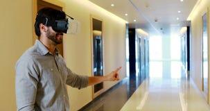 Executivo masculino que usa auriculares da realidade virtual no corredor vídeos de arquivo