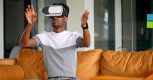 Executivo masculino que usa auriculares da realidade virtual no sofá 4k filme