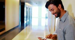 Executivo masculino que usa a tabuleta digital no corredor filme