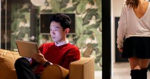 Executivo masculino que usa a tabuleta digital no sofá no escritório 4k vídeos de arquivo