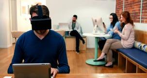 Executivo masculino que veste auriculares da realidade virtual ao usar a tabuleta digital vídeos de arquivo