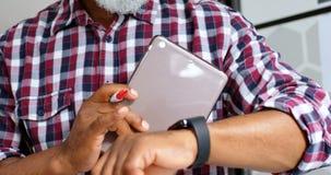Executivo masculino superior que usa o smartwatch ao trabalhar na tabuleta digital 4k filme