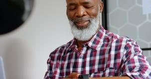 Executivo masculino superior que usa o smartwatch ao trabalhar no portátil 4k vídeos de arquivo