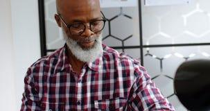 Executivo masculino superior que usa o smartwatch ao trabalhar no portátil 4k filme