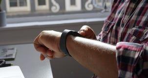 Executivo masculino superior que usa o smartwatch no escritório 4k vídeos de arquivo