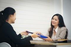 Executivo ou secretário feliz que dão a originais ao mulheres de negócios fotografia de stock royalty free