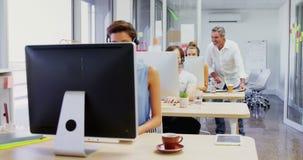 Executivo que ajuda a seus colegas ao trabalhar no computador 4k video estoque