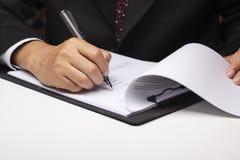 Executivo que assina no documento fotografia de stock