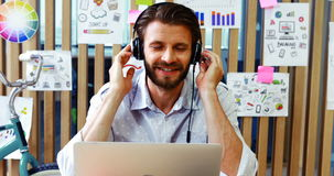 Executivo que escuta a música ao usar o portátil video estoque