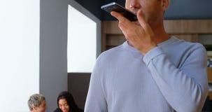 Executivo que fala no telefone celular quando colega que discute na tabuleta digital no fundo 4k video estoque
