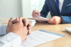 Executivo que lê um resumo durante uma entrevista de trabalho e um businessma fotografia de stock