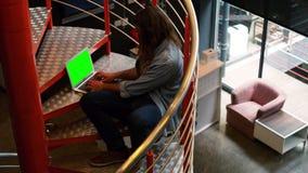 Executivo que senta-se em escadas e que trabalha no portátil vídeos de arquivo