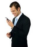 Executivo que sorri como lê a mensagem Imagens de Stock Royalty Free