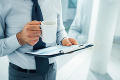 Executivo que trabalha durante sua ruptura de café imagens de stock royalty free