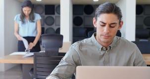Executivo que trabalha no portátil na mesa 4k video estoque