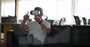 Executivo que usa auriculares da realidade virtual no sofá 4k video estoque