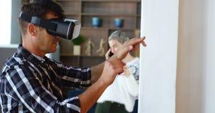 Executivo que usa auriculares da realidade virtual quando colega que fala no telefone celular no fundo 4k filme
