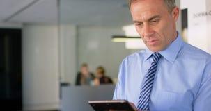 Executivo que usa a tabuleta digital no escritório 4k video estoque