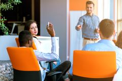 Executivos afro-americanos que levantam lá a mão acima em uma conferência para responder a uma pergunta fotos de stock