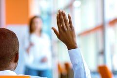 Executivos afro-americanos que levantam lá a mão acima em uma conferência para responder a uma pergunta imagens de stock royalty free