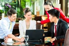 Executivos asiáticos na reunião na entrada do hotel Imagem de Stock