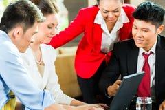 Executivos asiáticos que encontram-se na entrada do hotel Foto de Stock