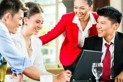 Executivos asiáticos que encontram-se na entrada do hotel imagens de stock