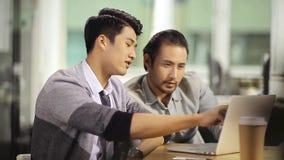 Executivos asiáticos que trabalham junto usando o portátil