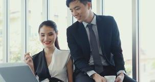 Executivos asiáticos que usam o portátil no escritório