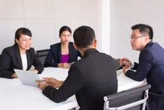 Executivos asi?ticos na reuni?o da sala, grupo da equipe que discute junto na confer?ncia no escrit?rio fotografia de stock