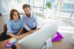 Executivos atentos que trabalham sobre o computador pessoal na mesa fotos de stock royalty free