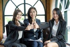 Executivos bem sucedidos com a sustentação polegares acima e smili imagens de stock royalty free