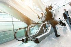 Executivos borrados que andam em uma escada rolante fotografia de stock royalty free