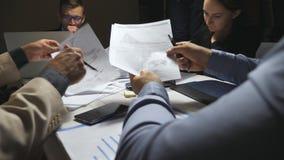 Executivos cansados que sentam-se na tabela e que discutem cartas e gráficos da renda no fim do dia de trabalho colegas vídeos de arquivo