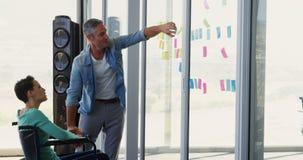 Executivos caucasianos que discutem sobre notas pegajosas na parede de vidro no escritório 4k filme