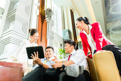 Executivos chineses asiáticos que encontram-se na entrada do hotel Foto de Stock Royalty Free